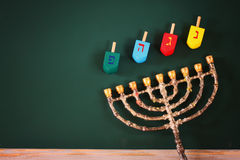 Image of jewish holiday Hanukkah with menorah (traditional Candelabra) and wooden colorful dreidels (spinning top) over chalkboard Stock Photos
