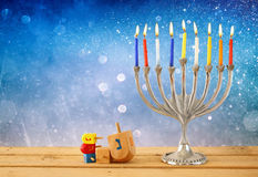 Low key image of jewish holiday Hanukkah with menorah (traditional Candelabra) and wooden dreidels (spinning top). Glitter background royalty free stock photography