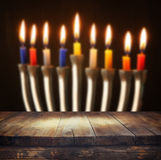 Image of jewish holiday Hanukkah background with menorah (traditional candelabra) Burning candles and wooden table Stock Images