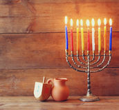 Low key image of jewish holiday Hanukkah with menorah (traditional Candelabra) and wooden dreidels (spinning top) Royalty Free Stock Images
