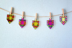 Image of jewish holiday Hanukkah with Stained-glass colorful dreidels (spinning top) hanging on a rope over wooden background Stock Photo