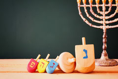 Low key image of jewish holiday Hanukkah with menorah (traditional Candelabra) and wooden dreidels spinning top Stock Image