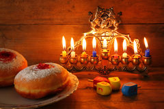 Image of jewish holiday Hanukkah with menorah (traditional Candelabra), donuts and wooden dreidels (spinning top) Royalty Free Stock Photo
