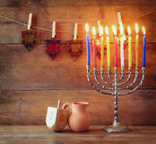 Low key image of jewish holiday Hanukkah with menorah (traditional Candelabra) and wooden dreidels (spinning top).  stock photography