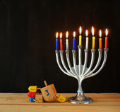 Image of jewish holiday Hanukkah with menorah (traditional Candelabra) and wooden dreidels (spinning top). retro filtered image Stock Photos