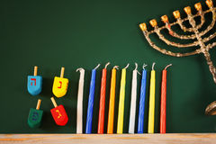 Low key image of jewish holiday Hanukkah with menorah (traditional Candelabra) and wooden dreidels spinning top Stock Images