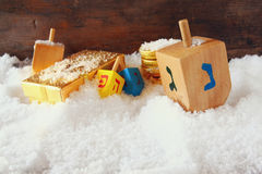Image of jewish holiday Hanukkah with wooden colorful dreidels (spinning top) and chocolate traditional coins over december snow Royalty Free Stock Photo