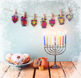 Image of jewish holiday Hanukkah with menorah (traditional Candelabra), donuts and wooden dreidels (spinning top). retro filtered. Image with snowflakes and