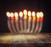 Image of jewish holiday Hanukkah background with menorah (traditional candelabra) Burning candles over wooden table Royalty Free Stock Images