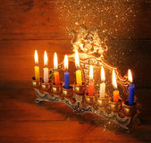 Image of jewish holiday Hanukkah background with menorah (traditional candelabra) and Burning candles with glitter overlay   Stock Photo
