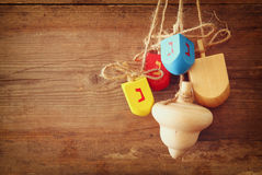 Image of jewish holiday Hanukkah with wooden colorful dreidels (spinning top) hanging on a rope over wooden background.