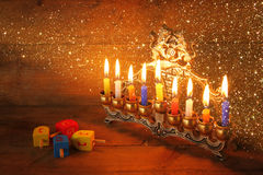 Low key image of jewish holiday Hanukkah with menorah (traditional Candelabra) and wooden dreidels (spinning top). glitter overlay Stock Photos