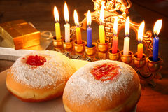 Image of jewish holiday Hanukkah with menorah (traditional Candelabra), donuts. retro filtered image with glitter overlay   Royalty Free Stock Image