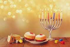 Image of jewish holiday Hanukkah with menorah (traditional Candelabra), donuts and wooden dreidels (spinning top) Stock Photo