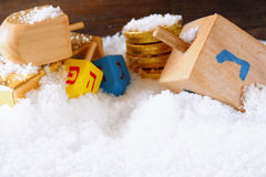 image of jewish holiday Hanukkah with wooden colorful dreidels (spinning top) and chocolate traditional coins over december snow Royalty Free Stock Photography