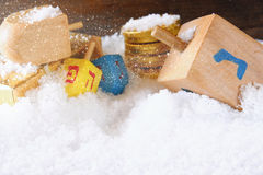 image of jewish holiday Hanukkah with wooden colorful dreidels (spinning top) and chocolate traditional coins over december snow Stock Photo