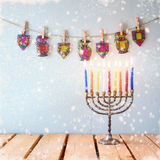 Image of jewish holiday Hanukkah with menorah (traditional Candelabra). glitter overlay with snowflakes
