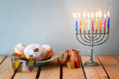 Image of jewish holiday Hanukkah with menorah (traditional Candelabra), donuts and wooden dreidels (spinning top) Stock Image