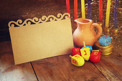 Image of jewish holiday Hanukkah with menorah (traditional Candelabra) and wooden dreidels (spinning top) with empty card  Stock Image