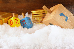 image of jewish holiday Hanukkah with wooden colorful dreidels (spinning top) and chocolate traditional coins over december snow.  Stock Photography
