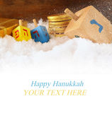 Image of jewish holiday Hanukkah with wooden colorful dreidels (spinning top) and chocolate traditional coins over december snow. Copy space