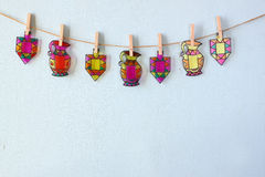image of Jewish holiday Hanukkah with Stained-glass colorful dreidels (spinning top) hanging on a rope over wooden background Stock Images