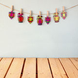 image of Jewish holiday Hanukkah with Stained-glass colorful dreidels (spinning top) hanging on a rope over wooden background Royalty Free Stock Images