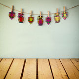 image of Jewish holiday Hanukkah with Stained-glass colorful dreidels (spinning top) hanging on a rope over wooden background Stock Image