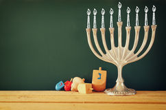 Image of jewish holiday Hanukkah with menorah (traditional Candelabra) and wooden dreidels (spinning top). retro filtered image   Royalty Free Stock Images