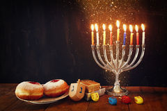 Image of jewish holiday Hanukkah with menorah (traditional Candelabra), donuts and wooden dreidels (spinning top). Image of jewish holiday Hanukkah with Stock Photo