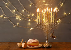 Image of jewish holiday Hanukkah background. Low key Image of jewish holiday Hanukkah with menorah (traditional Candelabra), donuts and wooden dreidel (spinning Stock Images