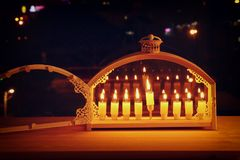 Image of jewish holiday Hanukkah background with menorah & x28;traditional candelabra& x29; and burning candles. In front of the window royalty free stock photos