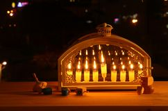 Image of jewish holiday Hanukkah background with menorah & x28;traditional candelabra& x29; and burning candles. In front of the window stock image