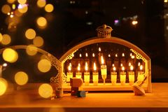 Image of jewish holiday Hanukkah background with menorah & x28;traditional candelabra& x29; and burning candles. In front of the window royalty free stock photography