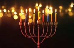 Image of jewish holiday Hanukkah background with menorah & x28;traditional candelabra& x29; and burning candles. Glitter overlay
