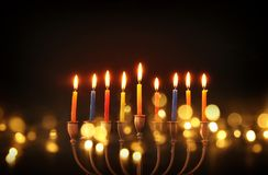 Image of jewish holiday Hanukkah background with menorah & x28;traditional candelabra& x29; and burning candles. Glitter overlay stock images