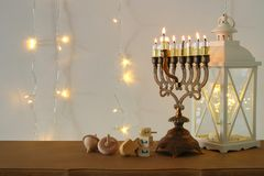 Image of jewish holiday Hanukkah background with traditional spinnig top, menorah & x28;traditional candelabra& x29;. And burning candles