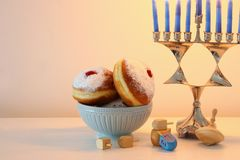 Image of jewish holiday Hanukkah background with traditional spinnig top, menorah & x28;traditional candelabra& x29; and donut. Image of jewish holiday Royalty Free Stock Photography