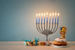 Image of jewish holiday Hanukkah background with traditional spinnig top, menorah & x28;traditional candelabra& x29;. And burning candles stock photo