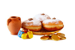 image of jewish holiday Hanukkah with donuts, traditional chocolate coins and wooden dreidels (spinning top). isolated on white   Stock Photo