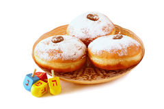 Image of jewish holiday Hanukkah with donuts and wooden dreidels (spinning top). isolated on white. Royalty Free Stock Images