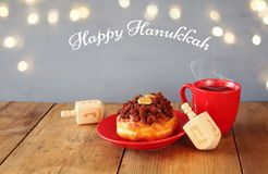 image of jewish holiday Hanukkah with donuts, wooden spinning top and cup of hot chocolate Stock Photos