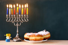 Image of jewish holiday Hanukkah. With menorah (traditional Candelabra), donut and wooden dreidel (spinning top