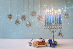 Image of jewish holiday Hanukkah with menorah. (traditional Candelabra), donut and wooden dreidel (spinning top Stock Photo
