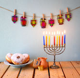 Image of jewish holiday Hanukkah with menorah (traditional Candelabra), donuts and wooden dreidels (spinning top). glitter backgro Stock Images