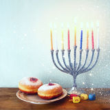Image of jewish holiday Hanukkah with menorah (traditional Candelabra), donuts and wooden dreidels (spinning top). retro filtered Stock Image