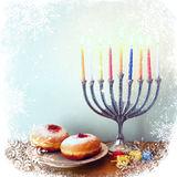 Image of jewish holiday Hanukkah with menorah (traditional Candelabra), donuts and wooden dreidels (spinning top). retro filtered. Image with glitter and Royalty Free Stock Image