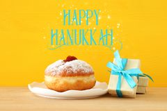 Image of jewish holiday Hanukkah with present box and traditional doughnut on the table. royalty free stock image