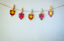 Image of jewish holiday Hanukkah with Stained-glass colorful dreidels (spinning top) hanging on a rope over wooden background. Stock Image