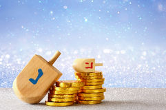 Image of jewish holiday Hanukkah with wooden dreidel. (spinning top) and chocolate coins on the glitter background